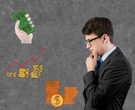 businessman thinking and coin with chart drawing on wall photo