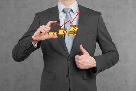 businessman in suit holding coin with chart photo
