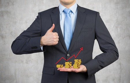 businessman holding coin with chart and showing thumb up photo
