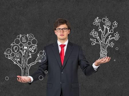 businessman holding two drawing tree photo