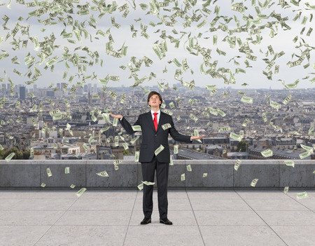 american banker: businessman standing on roof and catching falling dollar bills Stock Photo
