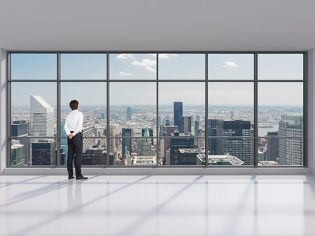 young businessman standing in big modern office photo