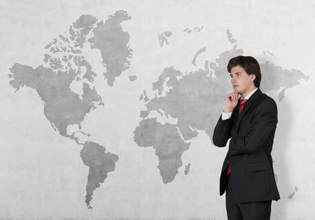 world thinking: businessman thinking and world map on wall Stock Photo