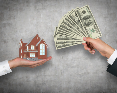 灰色の背景に住宅のお金を与えることを手します。