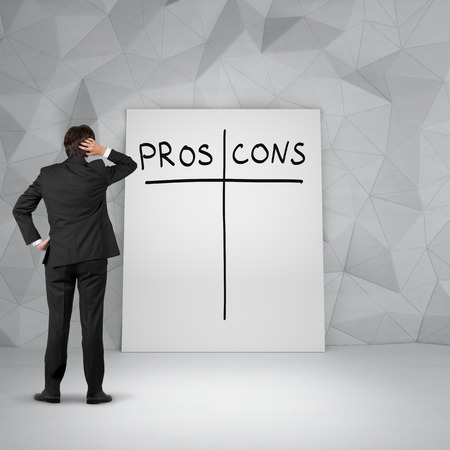 cons: businessman in room looking to poster with pros and cons Stock Photo