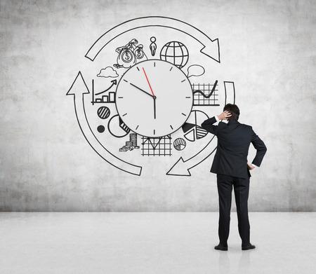 壁にビジネスの時間の概念を描画している実業家