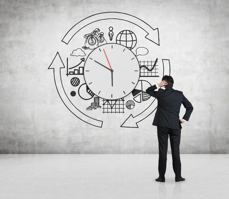businessman looking to drawing business time concept on wall 스톡 콘텐츠