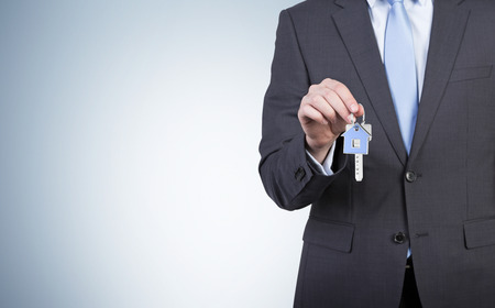 company secrets: Businessman is holding a key isolated on blue