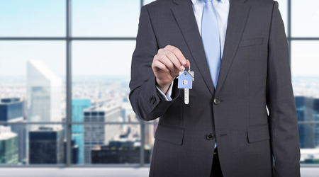 company ownership: Businessman is holding a key as a metaphor of pure success. Stock Photo