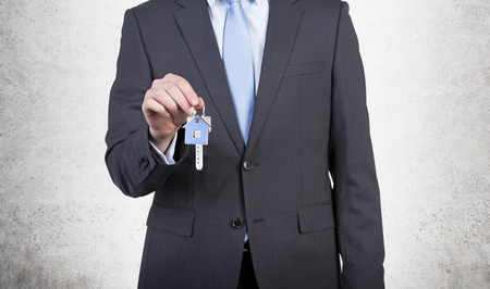 company ownership: Businessman is holding a key isolated on gray Stock Photo