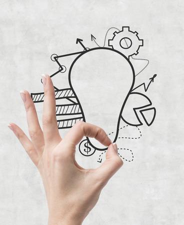 ok symbol: mano mostrando il simbolo OK e disegno lampada con grafico