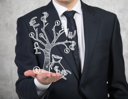businessman holding drawing money tree Stock Photo