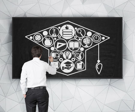 alumnus: businessman drawing business icon in form bachelor cap on black board Stock Photo