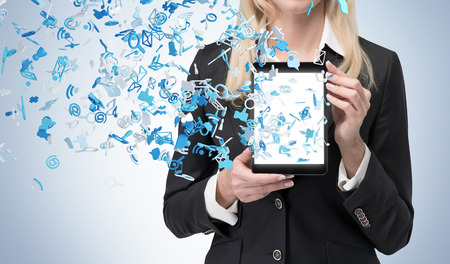 social media: businesswoman holding touch pad with social media icon