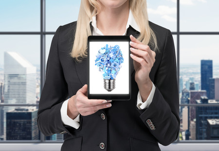 businesswoman holding tablet with social media icon in form lamp photo
