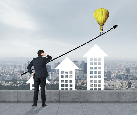 businessman looking to baloon with building chart photo