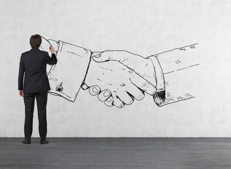 trust people: businessman in room drawing handshake on wall