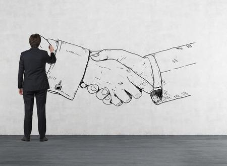 partnerships: businessman in room drawing handshake on wall