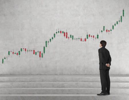 gripping bars: businessman looking to candle chart drawing on wall Stock Photo