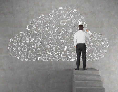 and clouds: young businessman drawing business icon in form cloud