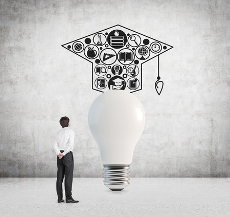 alumnus: businessman looking to bulb with bachelor cap Stock Photo