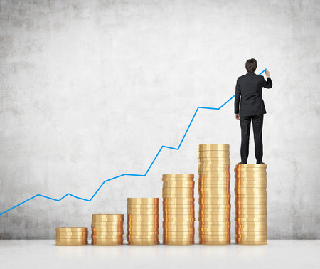 Business graph: businessman drawing chart standing on gold coins