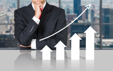 professional: businessman thinking and looking to chart on table Stock Photo