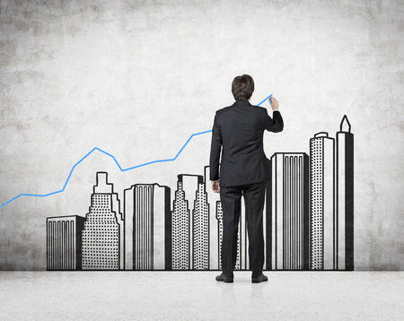 investment ideas: businessman drawing chart and buildings on wall