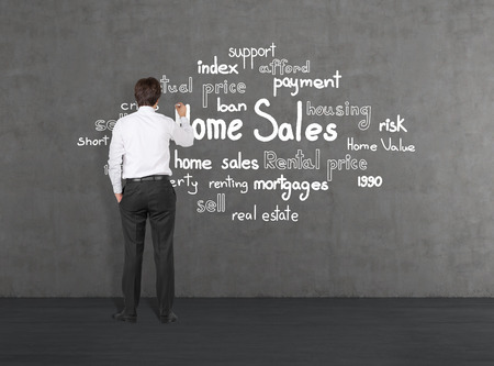 Young businessman drawing  home sales photo