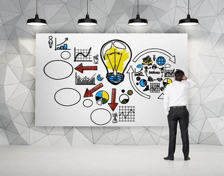 strategy diagram: businessman looking to drawing business strategy on poster Stock Photo