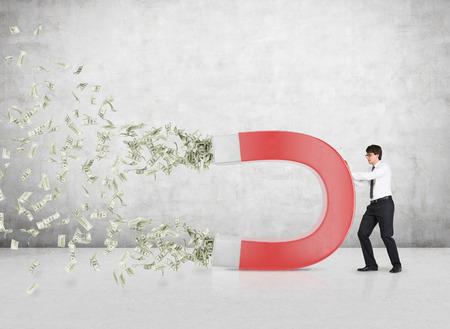 zakenman trekt geld met een grote rode magneet Stockfoto