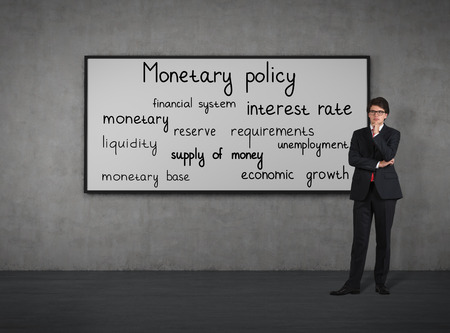 Businessman think about monetary policy at the blackboard Stock Photo