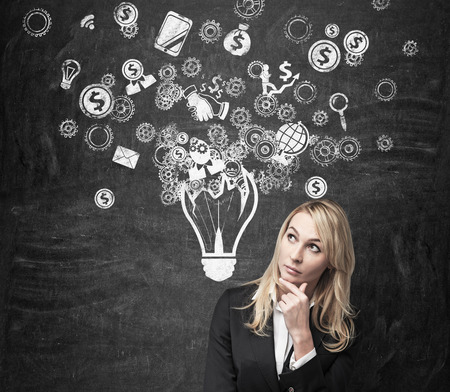 business solutions: businesswoman thinking and drawing business icon in form lamp Stock Photo
