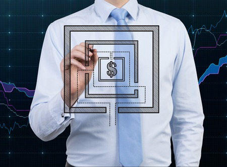 young businessman drawing maze with dollar symbol photo