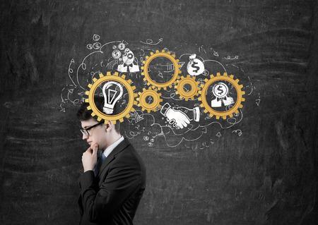 engranajes: el pensamiento de negocios con engranajes de oro en la cabeza