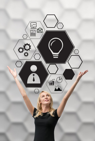 happy businesswoman looking on business icon over head photo