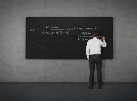 black board: businessman writing formula on the board with chalk Stock Photo
