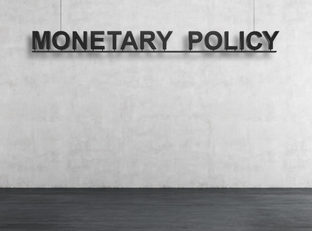 monetary policy: black monetary policy on white wall, close up
