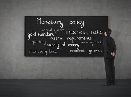 monetary policy: Businessman think about monetary policy at the blackboard Stock Photo