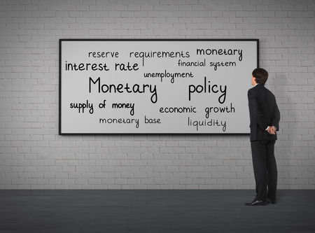 monetary policy: Businessman looking to monetary policy at the placard