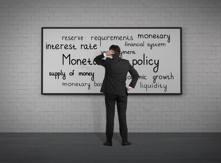 monetary policy: Businessman looking to monetary policy at blackboard Stock Photo