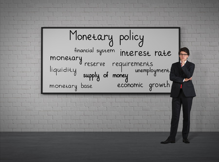 think about: Businessman think about monetary policy at the placard Stock Photo
