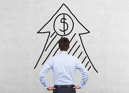 drawing arrow: businessman looking to drawing arrow with dollar on wall Stock Photo