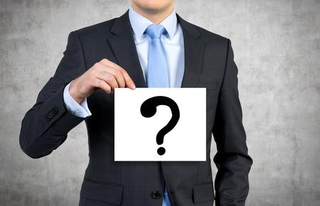 punto interrogativo: uomo d'affari che tiene manifesto con contrassegno disegno domanda Archivio Fotografico