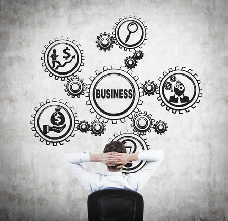 man looking on drawing gears with business icons photo