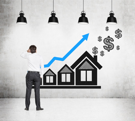 businessman looking on drawing chart and house on wall photo