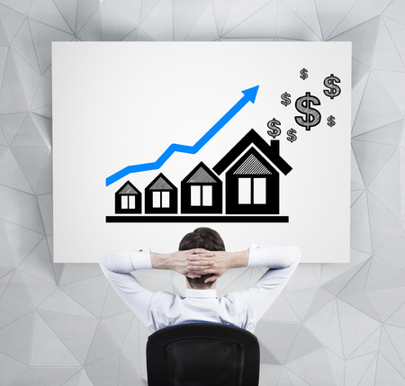 businessman in office looking on drawing blue chart  and house photo