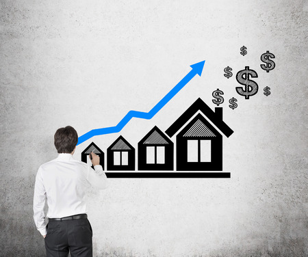 young businessman drawing chart and house on wall photo