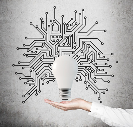 microcircuit: hand holding lightbulb with microcircuit on gray background Stock Photo