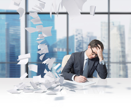 tax: businessman working in office and falling tax papers
